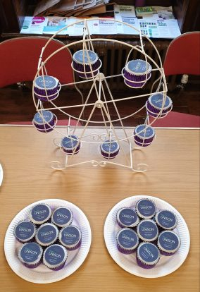 A ferris wheel full of cupcakes with more cupcakes on plates in front of it
