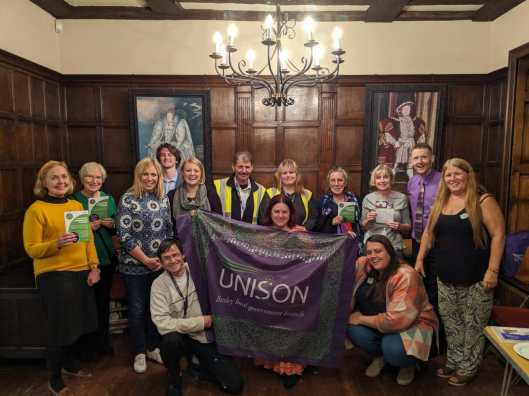 Lots of members who attended the Local Service Champions 2019 event posing with our branch banner